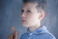 Boy behind the window Royalty Free Stock Image