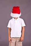 Boy being silly with Santa hat during Christmas Royalty Free Stock Photo
