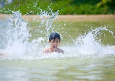 Boy being splashed in the water park Royalty Free Stock Photo