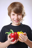 Boy with bell peppers. Smiling boy with ripe bell peppers Royalty Free Stock Photos