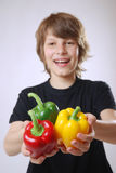 Boy with bell peppers. Smiling boy with ripe bell peppers Stock Photo
