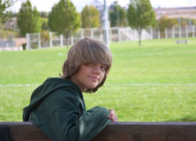 Boy on Bench. Young teen boy with long, shaggy hair, sitting on a bench in front of a park with green grass and trees Stock Images