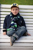 Boy on a Bench. Young boy sitting on a bench in a park Royalty Free Stock Photos