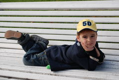Boy on a Bench. Young boy sitting on a bench in a park Royalty Free Stock Photo