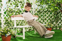 Boy on a bench in the garden Stock Images