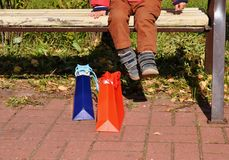 A boy on a bench with packages resting after shopping. stock image