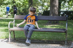 Boy on bench in park. Teenager is thinking about his behavior Stock Photos