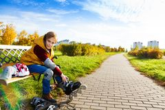 Boy on the bench putting on roller skates Stock Image