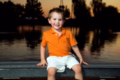 Boy On Bench at Sunset. A young boy in a bright orange shirt sits on a bench at sunset. He has bright, blue eyes and a big smile Royalty Free Stock Photos