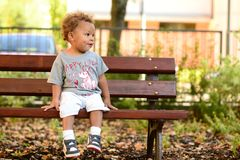 Boy on bench waiting. Little biracial boy is sitting on bech, looking to his left side and waiting patiently Royalty Free Stock Photos