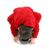 Boy Bent Over Reading Bathroom Scale. Small boy in red sweats on bathroom scale.  Bent over to get a close look Royalty Free Stock Photo