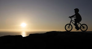 Boy and bicycle. At sunset Stock Photography