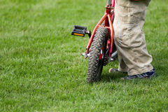 Boy with bicycle. Detail of a boy with a bicycle on green grass Stock Photography