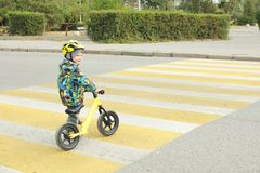 A boy with a bicycle crosses a pedestrian crossing with yellow markings Stock Images