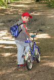 Boy with bicycle glancing back. Little boy with bicycle glancing back on forest path Royalty Free Stock Images