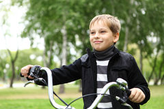 Boy on a bicycle in the green park Stock Photos
