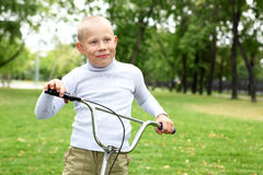 Boy on a bicycle in the green park Royalty Free Stock Photos
