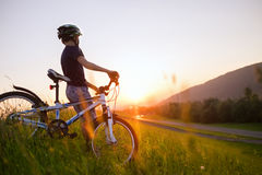 Boy with bicycle looks on sunset Stock Photos
