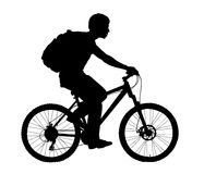 Boy with a bicycle. A boy rides a bicycle with a backpack Stock Images