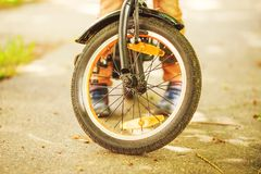 Boy with a bicycle on the street. Wheel of a children`s bicycle stock photography