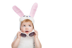 Boy with big blue eyes dressed in Easter bunny ears take off sunglasses and looking up Stock Image