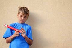 Boy with big pencil stands near wall Royalty Free Stock Image