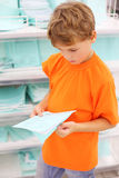 Boy in big shop chooses school notebook Royalty Free Stock Images
