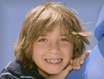 Boy with Big Smile. Head shot of an eight year old boy with bright brown eyes and hair, and toothy big smile showing gaps in the teeth, highlighted by the sun as Stock Photography