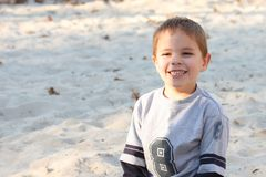 Boy with a big smile in sand Stock Image