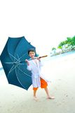 Boy with big umbrella standing at the beach, Royalty Free Stock Images