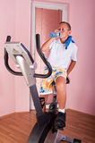 Boy on bike. Happy boy exercise on spinning bicycle at home Royalty Free Stock Image