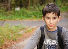 Boy on the bike. The boy with a Bicycle stands in a forest road Stock Photo