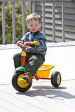 Boy on bike. Young boy sitting on toy bike outside Royalty Free Stock Photo