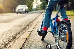 Boy on bike. A boy on bike and a car on the road Stock Image