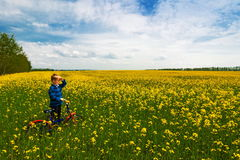 Boy with bike on country field with flowers in sunny day. In spring Royalty Free Stock Images