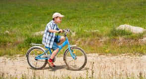 Boy with bike on a country road through meadow Royalty Free Stock Image