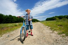 Boy with bike on a country road through meadow Stock Images