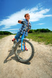 Boy with bike on a country road through meadow Royalty Free Stock Photo