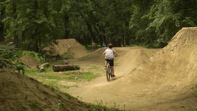 The boy on the bike. Cyclist in the woods. Riding and jumping over obstacles. Bicycle Wheels come off the ground. June 5 stock video