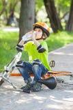 The boy in a bike helmet drinks water Stock Photo