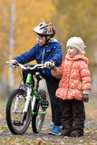 Boy on the bike with his sister Stock Images
