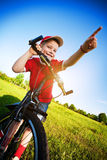 Boy on a bike points direction of motion Stock Image