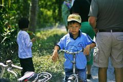 Boy on a bike. Portrait of an unsmiling boy in blue shirt and yellow cap on his bike in Mekong Delta, South Western Vietnam, jungle background Stock Photos