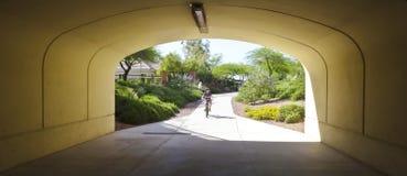 A Boy on a Bike Rides Toward a Tunnel Royalty Free Stock Photos