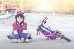 Boy with bike. Boy sitting on the floor with bike Royalty Free Stock Image