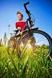 Boy with bike standing against the blue sky. Boy with his bike standing against the blue sky Royalty Free Stock Photography