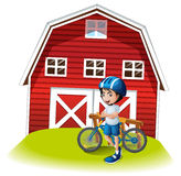 A boy with a bike standing in front of the farmhouse Royalty Free Stock Photos