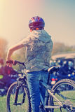 Boy on the bike in sunrise. Young boy with his bicycle and bikers in city street stock photography
