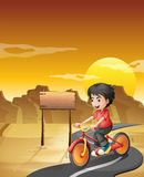 A boy biking at the desert with an empty signboard Royalty Free Stock Photography