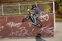 Boy is biking with the dirtbike in a bike park. At the halfpipe Royalty Free Stock Image
